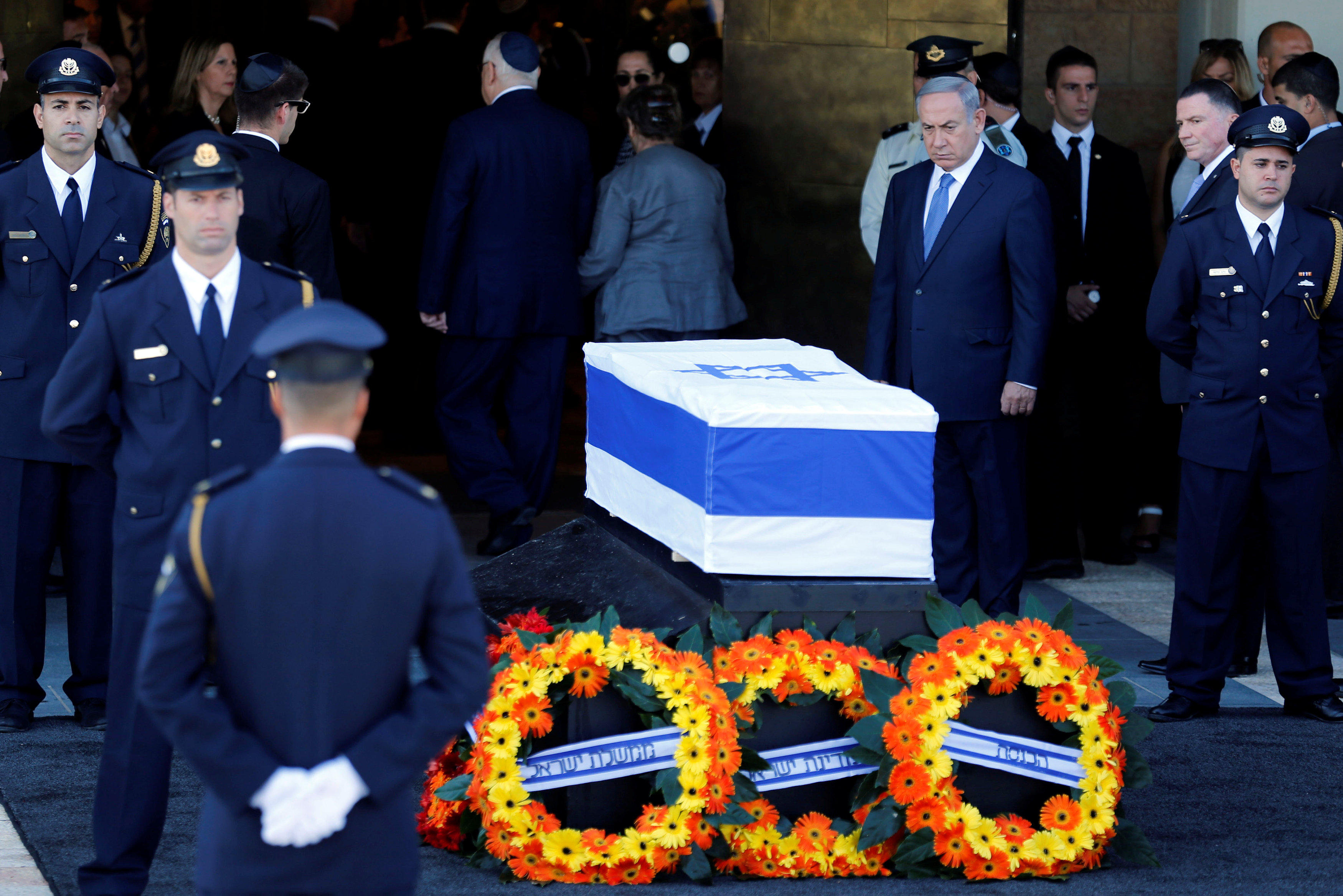Israeli Prime Minister Benjamin Netanyahu stands next to the flag-draped coffin of former Israeli President Shimon Peres, as he lies in state at the Knesset plaza, the Israeli parliament, in Jerusalem