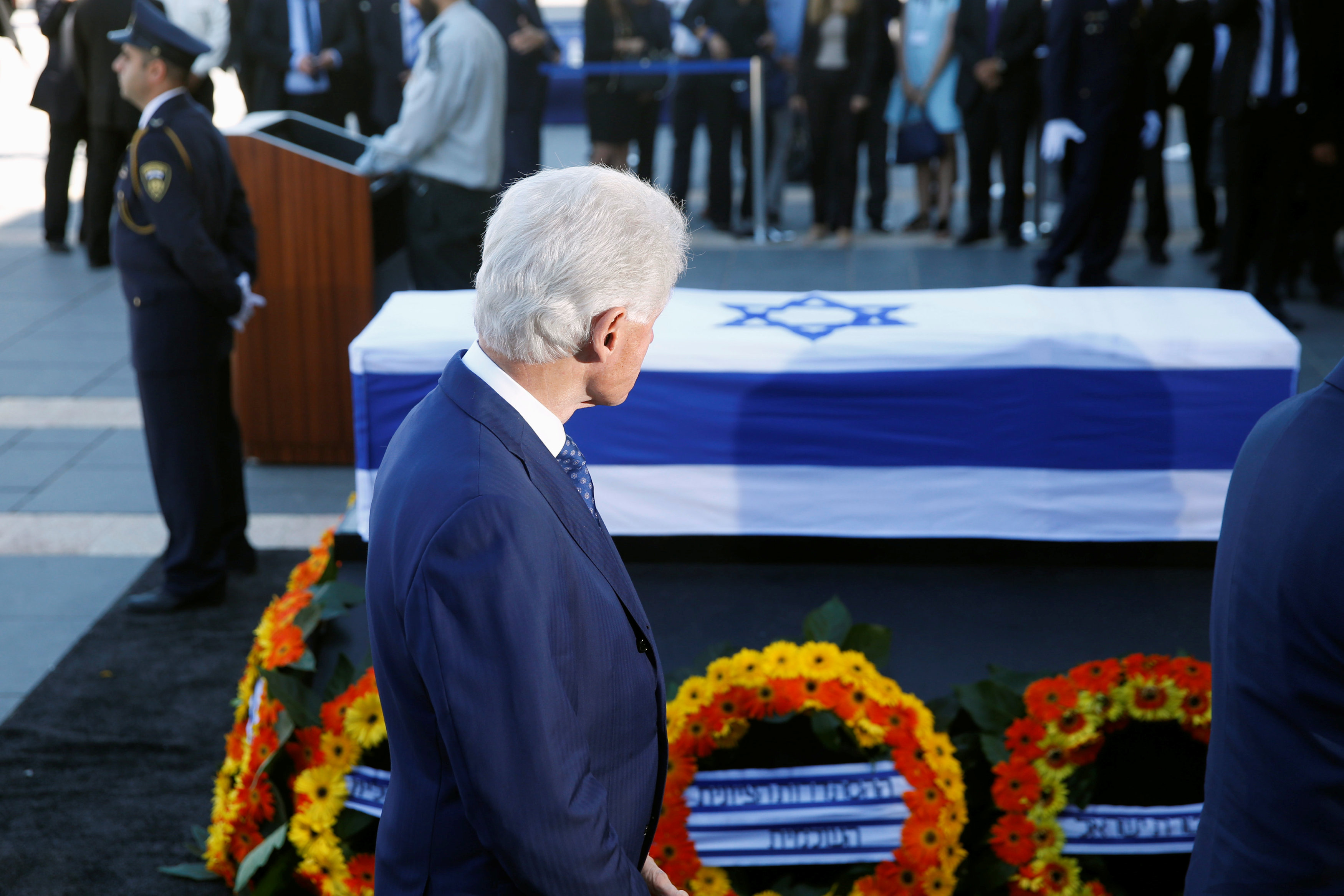 Former U.S. President Bill Clinton stands next to the flag-draped coffin of former Israeli President Shimon Peres, as he lies in state at the Knesset plaza, the Israeli parliament, in Jerusalem