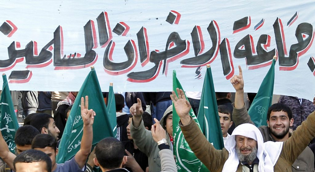 Members of the Muslim Brotherhood movement shout slogans as thousands of Jordanians demonstrated peacefully in Amman and other cities after weekly prayers on Friday to press for political and economic reform, and demanding that the government resign. Banner reads: The Islamic Brotherhood. AFP PHOTO/KHALIL MAZRAAWI (Photo credit should read KHALIL MAZRAAWI/AFP/Getty Images)