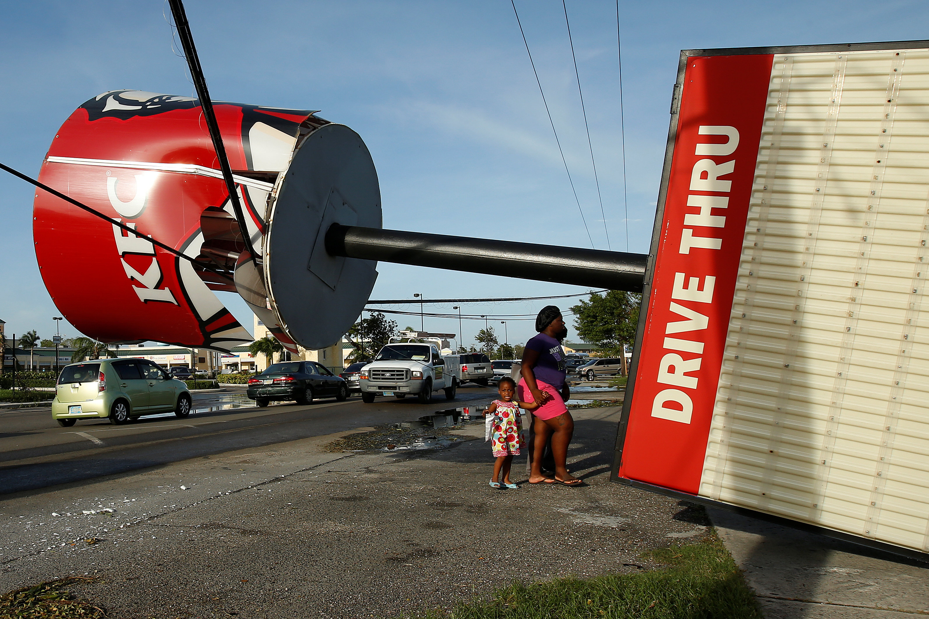 People walk under a broken Kentucky Fried Chicken sign that blew over in Hurricane Matthew in Nassau, Bahamas October 7, 2016. REUTERS/Carlo Allegri     TPX IMAGES OF THE DAY