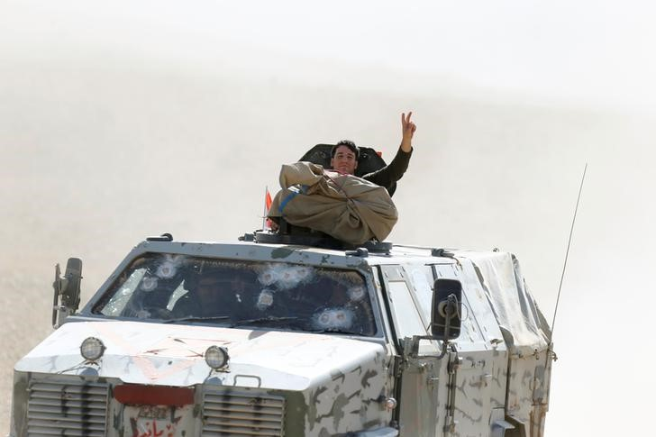 A member of Peshmerga forces gestures from the top of the military vehicle in the east of Mosul during operation to attack Islamic State militants in Mosul