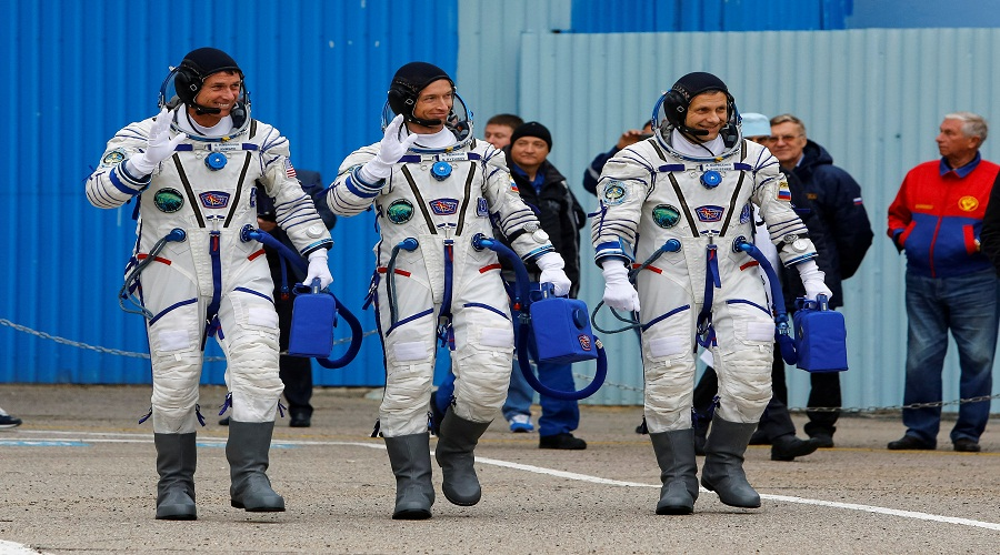 The International Space Station (ISS) crew members Kimbrough of the U.S., Ryzhikov and Borisenko of Russia walk after donning space suits at the Baikonur cosmodrome, Kazakhstan