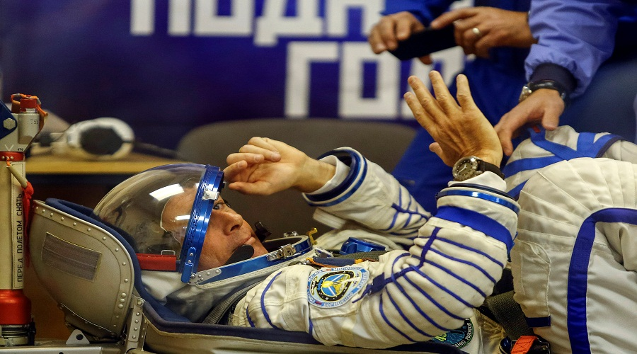 The International Space Station crew member Kimbrough of the U.S. waves during a check of his spacesuit at the Baikonur cosmodrome, Kazakhstan