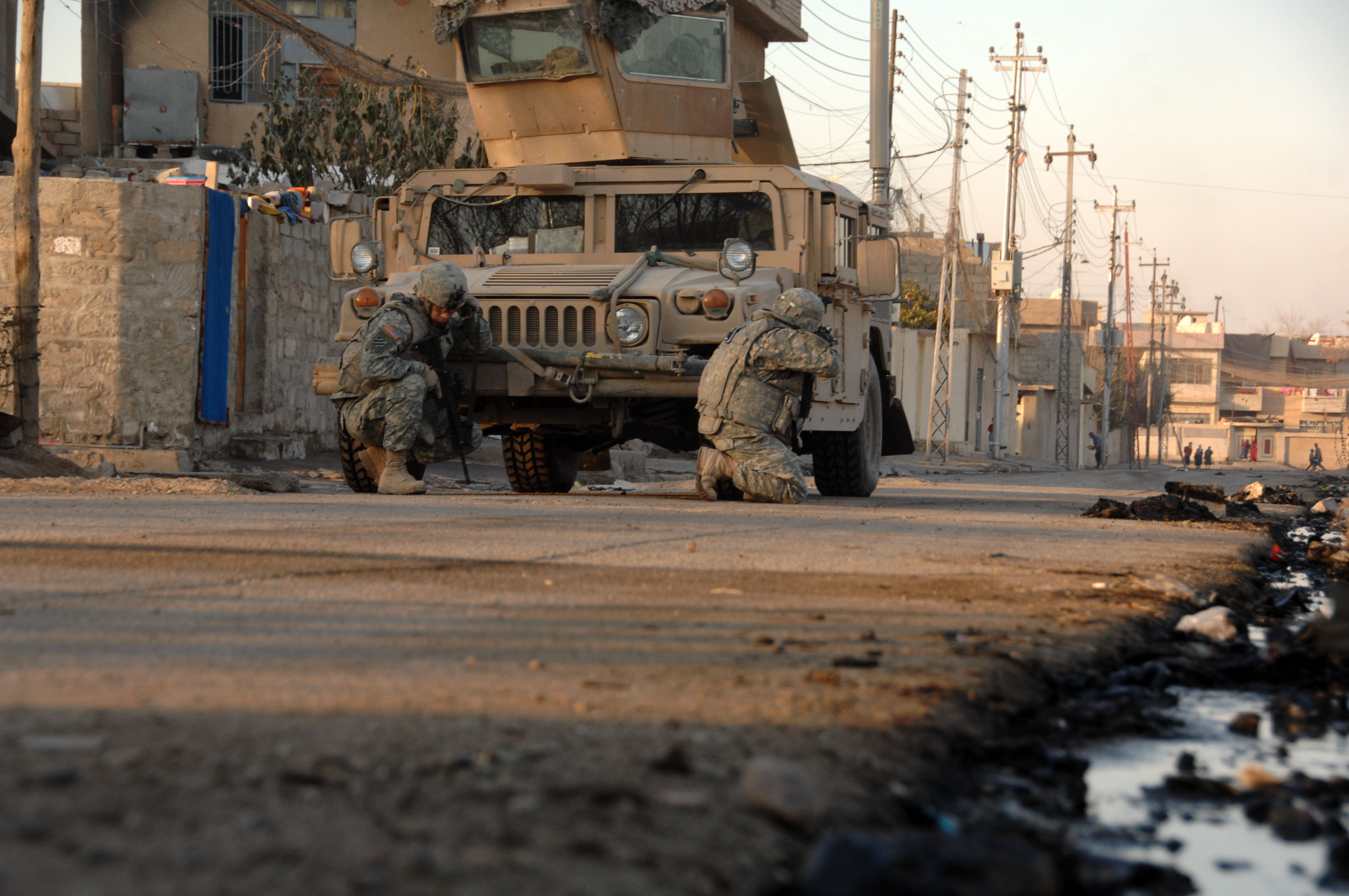 U.S. Army Soldiers, attached to Heavy Company, 3rd Squadron, 3rd Armored Cavalry Regiment, take cover behind their vehicle as they hear small arms fire open up in the distance in Mosul, Iraq, on Jan. 17, 2008. (U.S. Army photo by Spc. Kieran Cuddihy) (Released)