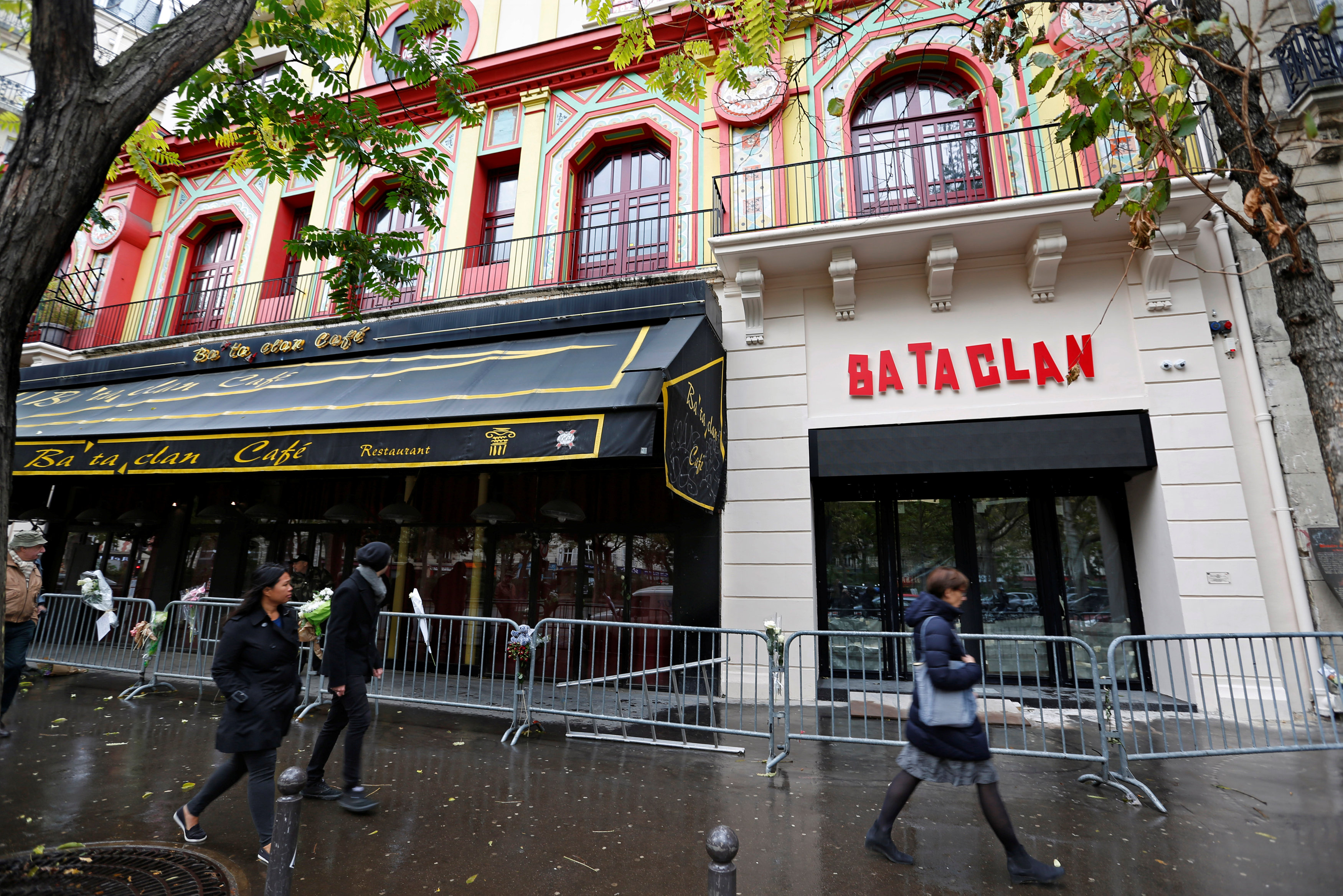 People walk past the Bataclan Cafe and the new facade of the Bataclan concert hall almost one year after a series of attacks at several sites in Paris