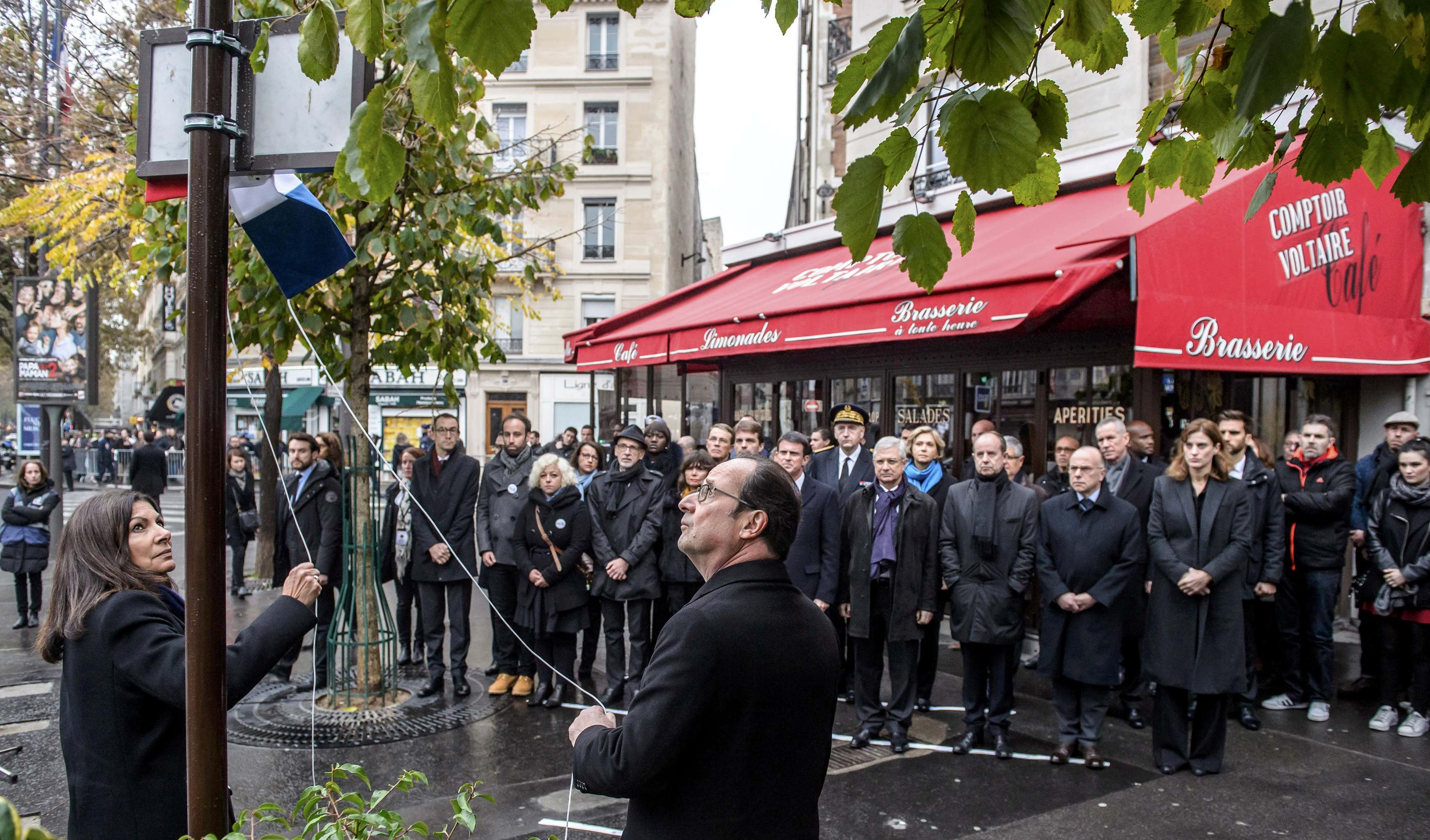 French President Francois Hollande and Paris Mayor Anne Hidalgo unveil a commemorative plaque in front of the Comptoir Voltaire cafe and restaurant