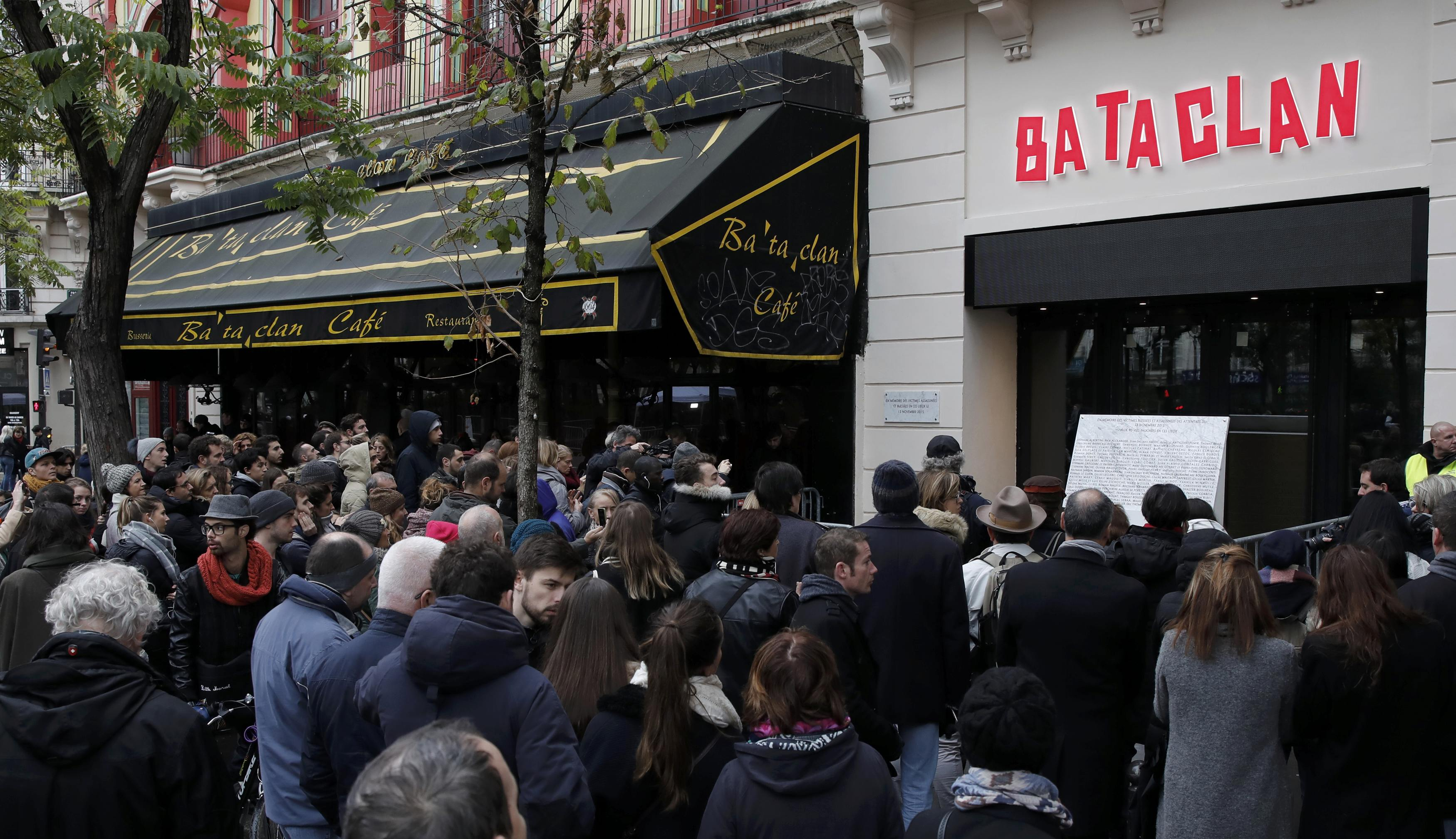 People gather in next to a commemorative plaque unveiled by French President Francois Hollande and Paris Mayor Anne Hidalgoin front of the Bataclan concert hall