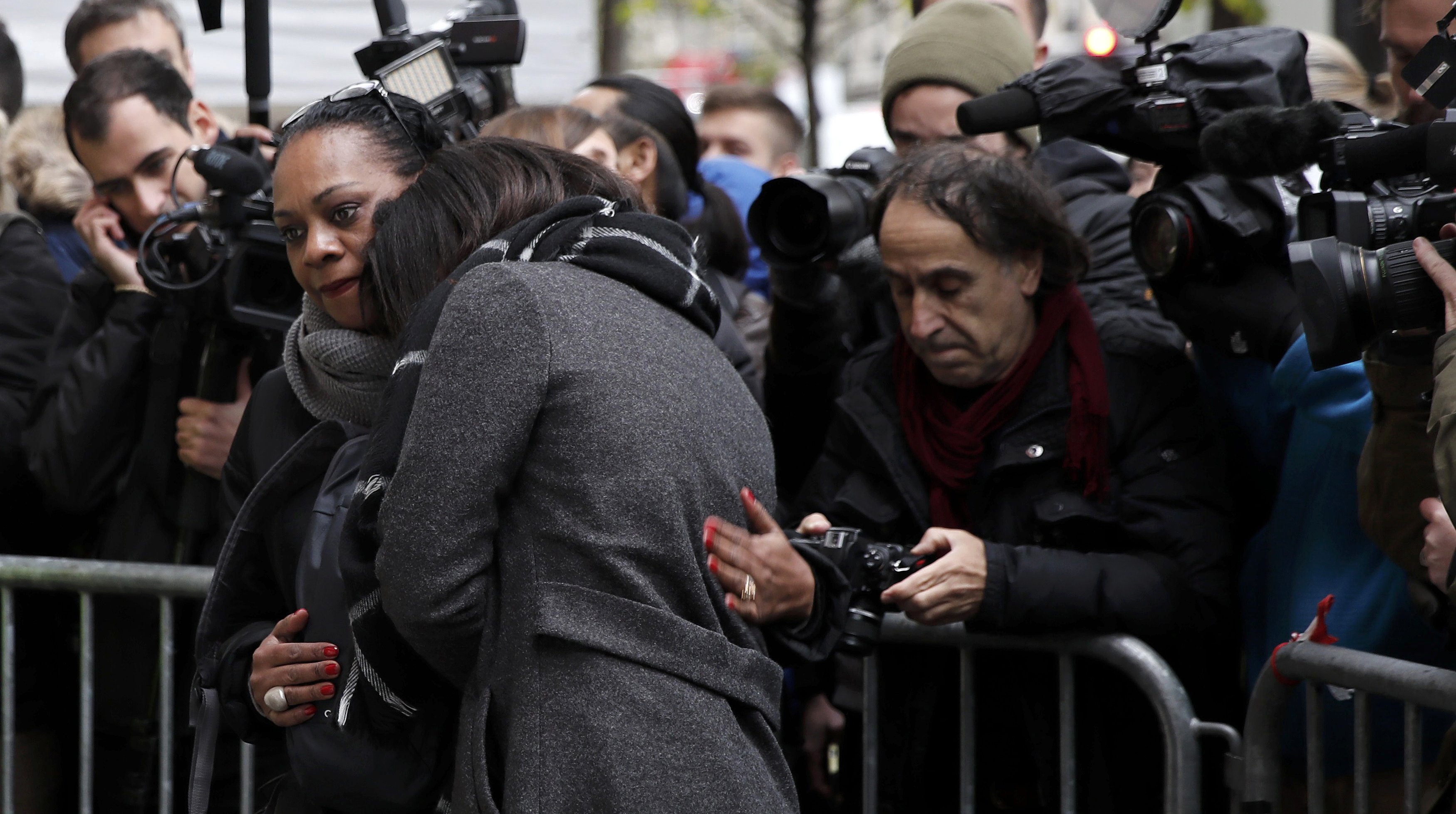 Relatives of the victims gather next to a commemorative plaque unveiled by French President Francois Hollande and Paris Mayor Anne Hidalgo in front of the Bataclan concert hall