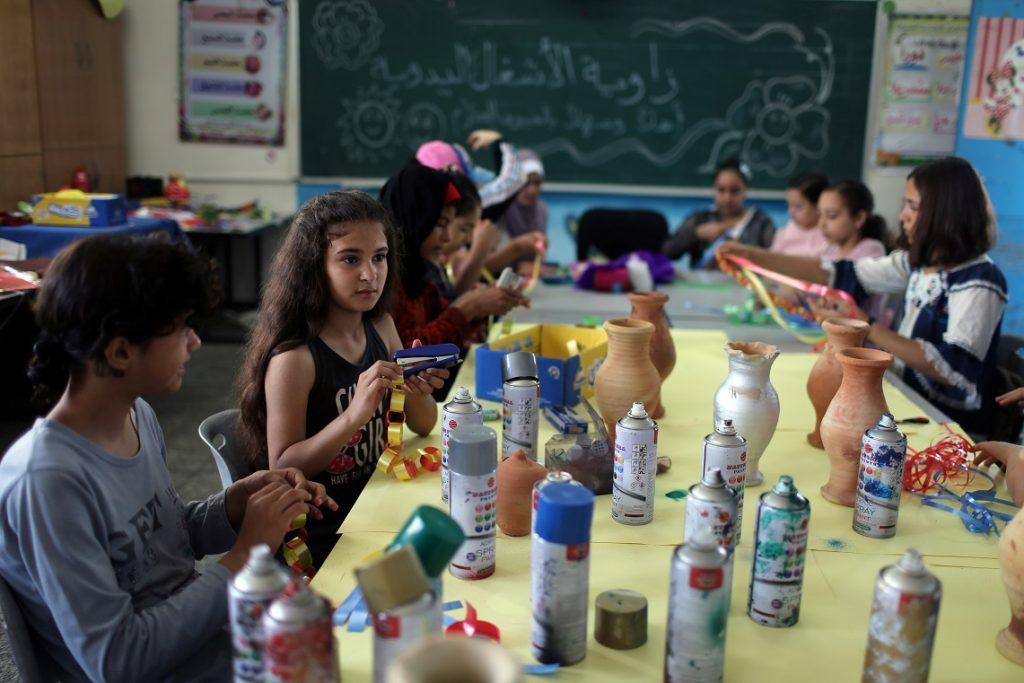 أطفال يمارسون أنشطة الرسم والفن داخل المعسكر الصيفي