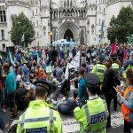 احتجاجات على تغير المناخ في وسط لندن وناشطة تتسلق بوابة وزارة النقل