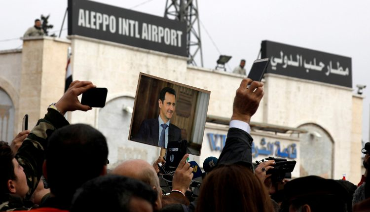 People hold up a picture of Syria's President al-Assad at Aleppo international airport